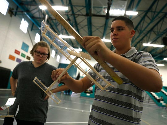 Farmington High School ninth-grader Kasadi Dixon, left, watches Piedra Vista ninth-grader Lucas Salazar measure his plane for the Wright Stuff airplane competition Saturday during the 2016 Northwest Regional Science Olympiad at Mesa View Middle School in Farmington.