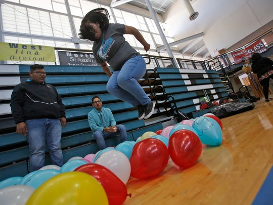 Kaylee Wood jumps on a balloon as her classmates, Eric Woody, left, and Nachae Nez, look on during an International Week activity on Wednesday at Navajo Preparatory School in Farmington. Every 15 minutes, students popped several balloons that represented smoking deaths.
