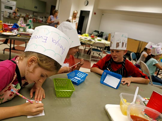 Kids write down ingredients June 8, 2015, during a