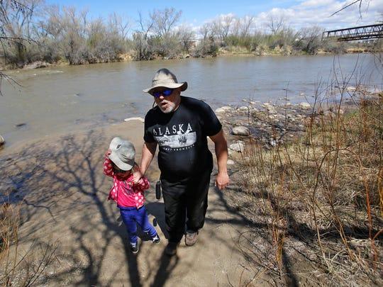 John Lehleither walks with his granddaughter Charlotte Dalton Tuesday along the banks of the Animas River during a Riverside Nature Center picnic at Animas Park in Farmington.