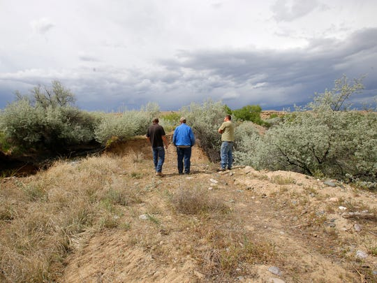 From left, Chris Ivey, Harold Chamberlin and Mike Meidinger look down at the spot where a large portion of bank along the Bloomfield Irrigation District Ditch collapsed on Monday. The eroded bank is located off County Road 4655 in Blanco.