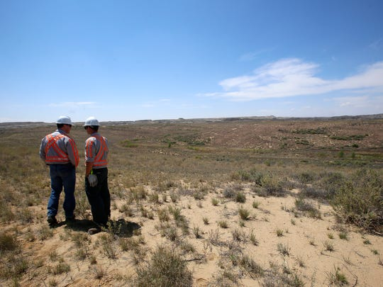 BHP Billiton General Manager Shawn Goeckner, left, and BHP Billiton Superintendent of Drilling and Blasting Josha Kantor examine a portion of the Navajo Mine's Chinde Reclamation area in Fruitland on May 26.