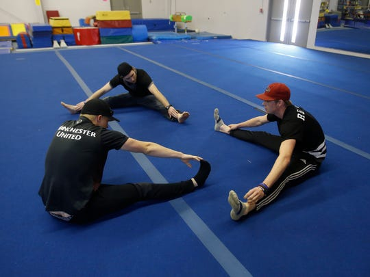 From left, JD Brown, Joshua Blackman and instructor Taylor Winer stretch before parkour practice on May 7 at Farmington Gymnastics Academy.