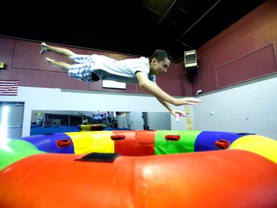 Mark Yerkey dives over an obstacle during parkour practice