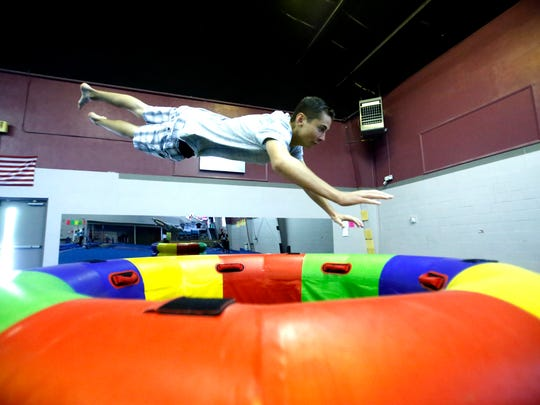 Mark Yerkey dives over an obstacle during parkour practice on May 7 at Farmington Gymnastics Academy.