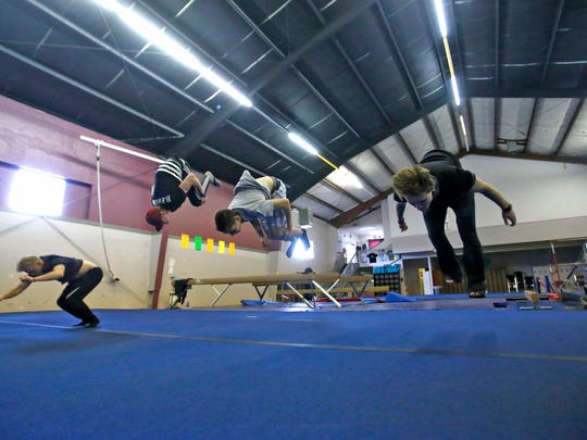 From left, JD Brown, parkour class instructor Taylor Winer, Mark Yerkey and Taylor Winer practice on May 7 at Farmington Gymnastics Academy.