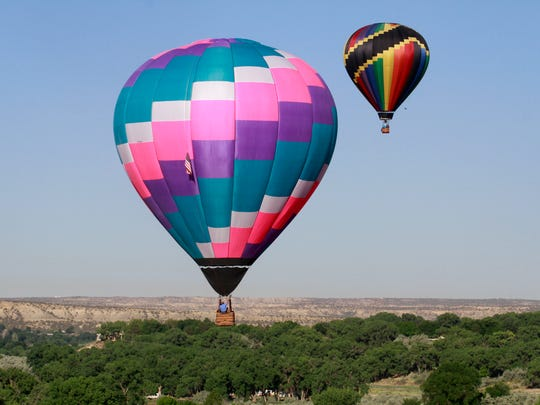 Hot-air balloons fly over the San Juan River on Friday west of Bloomfield during the San Juan River Balloon Rally.