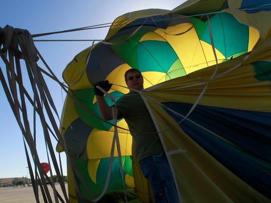 Neil Johnson, a member of the Sun Dagger crew, helps break down his team's balloon on Friday at the San Juan River Balloon Rally in Bloomfield.