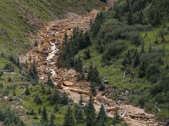 Debris from the Gold King Mine spill cascades down a mountainside on Aug. 10 north of Silverton, Colo.