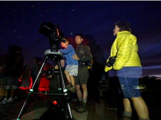 Visitors to Chaco Culture National Historic Park look through a telescope on Friday at the park.