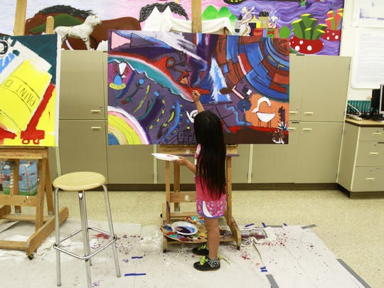 "Cyra John works on a painting on July 9, 2014, during a session of ""Dahayóígíí: A Cultural Youth Art Event"" at Shiprock High School."