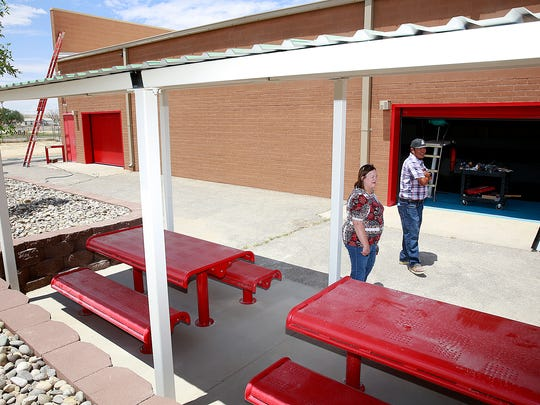 From left, Waynette Danley, a building and construction specialist for the Central Consolidated School District, and Thomas Montanez, a superintendent at B&M Cillessen Construction Co.,  stand outside the renovated pool facility at Shiprock High School on Thursday.