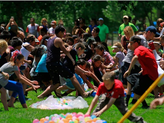 Participants race to gather water balloons during a water balloon fight on Monday as part of Freedom Days' Party in the Park at Brookside Park in Farmington.