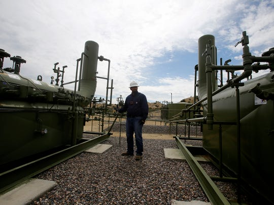 ConocoPhillips optimization technician Juan Cardenas provides a tour of one of the company's oil and gas facilities on  June 30 at a site in Aztec. The company has been working to reduce its emissions.