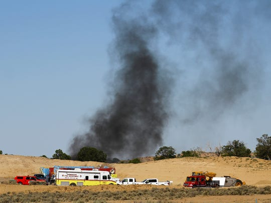 Crews stage on Tuesday near the site of a fire at a