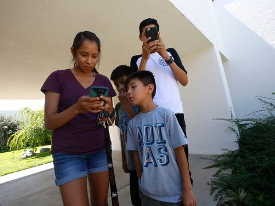Paris Chee, left, Elias Largo, Myles Largo and Bradon Jack play Pokémon Go Thursday at San Juan College.