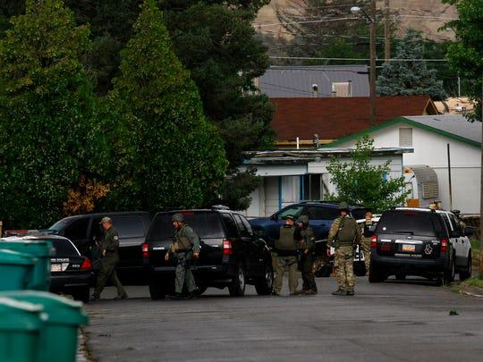 Farmington police officers on Friday surround a home on Kayenta Drive in Farmington.