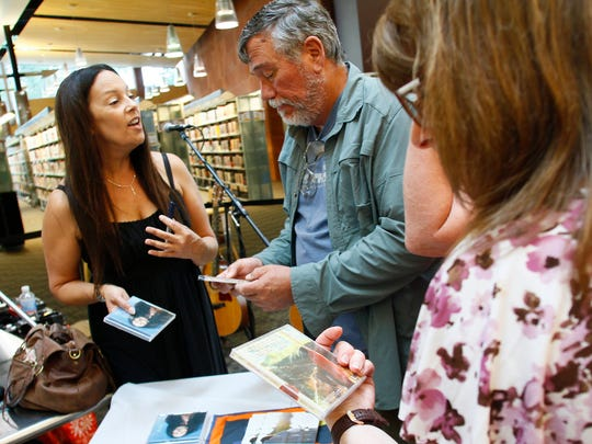 Jill Cohn talks with audience member Mickey Ginn after her June 5, 2015, performance at the Farmington Public Library.