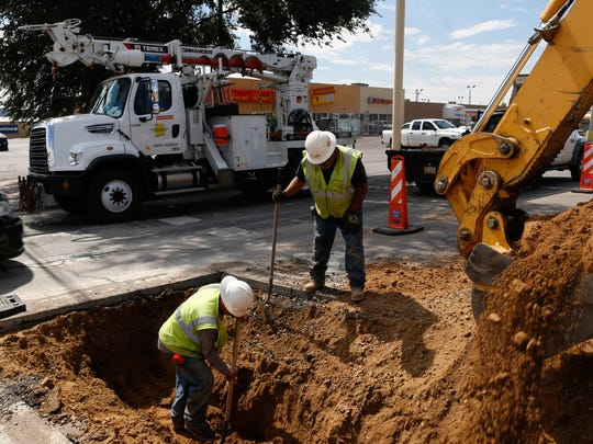 TRC Construction workers install electric lines Wednesday at the intersection of North Hutton Avenue and East 20th Street in Farmington.