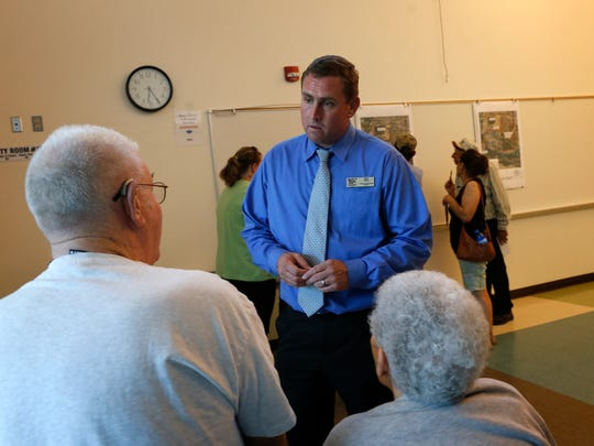 San Juan County Chief Operation Officer Mike Stark, center, talks with Totah subdivision residents Archie Holmes and Margaret Clements during a meeting Thursday at the Sycamore Park Community Center in Farmington.