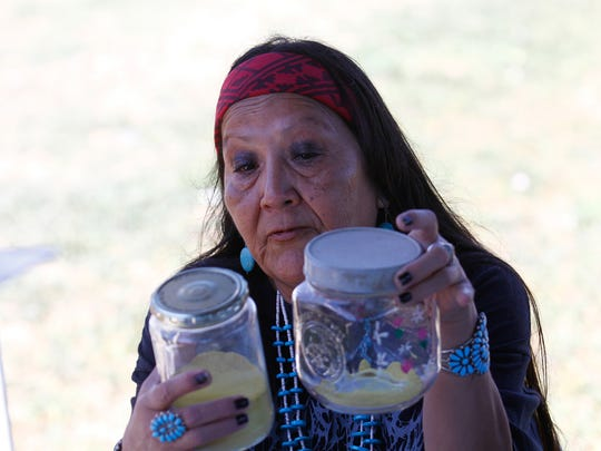 Cheryle Yazzie holds up jars containing corn pollen during a meeting with U.S. Sen. Tom Udall Friday at her home in Shiprock.