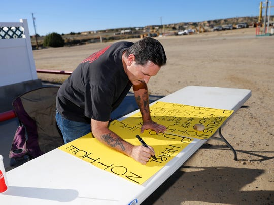 John Livingston makes a signs Friday at Dino's convenience store on Crouch Mesa alerting AV Water Co. customers to attend Wednesday's Public Regulation Commission hearing in Aztec.