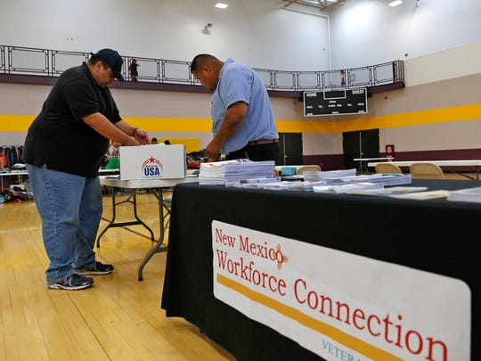From left, Thomas Muriel, a  Disabled Veterans Outreach Program specialist with New Mexico Workforce Connection, and Sheldon Howard, a local veterans employment representative with the agency, set up their table on Thursday for the San Juan County Homeless Veterans Stand Down at San Juan College's Health and Human Performance Center in Farmington.
