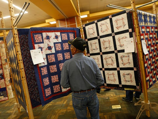 Veteran Teddy Smallcanyon admires his quilt Saturday during a ceremony at the San Juan Quilters Guild's annual show at the Farmington Civic Center.