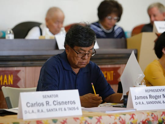 N.M. Rep. James Madalena, D-Jemez Pueblo, reviews a handout about the difference between sentences issued by state and federal courts during an Indian Affairs Committee meeting on Tuesday at the Tooh Haltsooí Chapter house in Sheep Springs.