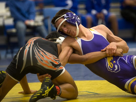 Kirtland Central's Raemondo Miles takes on a Miyamura wrestler in the 132-pound weight class on Friday during the Bloomfield Invitational at Bobcat Gym in Bloomfield.