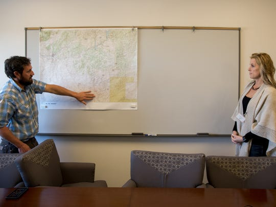 Bureau of Land Management wildlife biologist Neil Perry and WPX Regulatory Manager Heather Riley on Dec. 7 at the Bureau of Land Management office in Farmington talk about a mule deer study the company is funding.