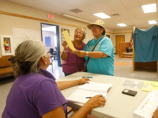 Donna Williams, left, and Dianna Yazzie-Nez look over a sample ballot on June 28 at the Coyote Canyon chapter house. In the special election, voters determined who would represent Bahastl'ah, Coyote Canyon, Mexican Springs, Naschitti and Tohatchi chapters on the Navajo Nation Council.