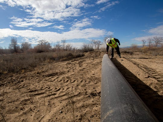 Gregory Bahe, operations supervisor for water and wastewater in the engineering, construction and operations division at Navajo Tribal Utility Authority, inspects a pipe on Wednesday that will be used to repair a ruptured pipeline in Shiprock.