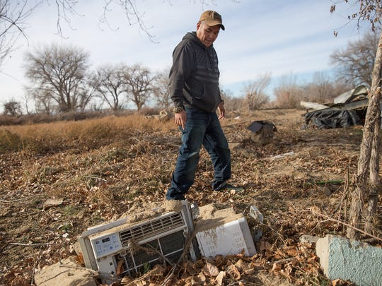 Derrick Woody points at the remains of his grandmother's air conditioner unit Wednesday at his family's former residence in Shiprock.