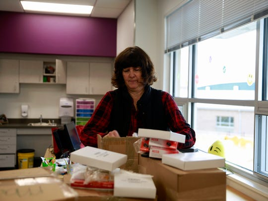 Fourth-grade teacher Vicky Mallow unpacks a box of supplies for her classroom on Monday at the new Judy Nelson Elementary School in Kirtland.