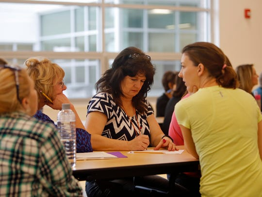 Denise Pierro, first-grade lead teacher, takes notes on Monday during a meeting for teachers and staff members inside the cafeteria at the new Judy Nelson Elementary School in Kirtland.