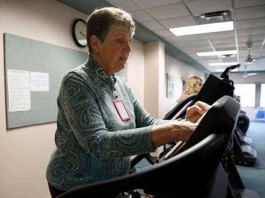 Pam Wilson uses the treadmill on Friday at the Bloomfield Fitness Center, located inside the city's Cultural Complex. The card now required to gain entry to the fitness center hangs around her neck.