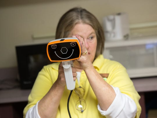 Marilyn Montoya of the Farmington Evening Lions Club holds an eye scanner during an eye test for students Wednesday at Central Primary School in Bloomfield.