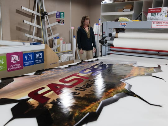 Kim Coufal, the franchise owner of FASTSIGNS in Farmington, talks on Monday about how the store produces its signs. The new store is located at 5150 College Blvd., Suite 204.