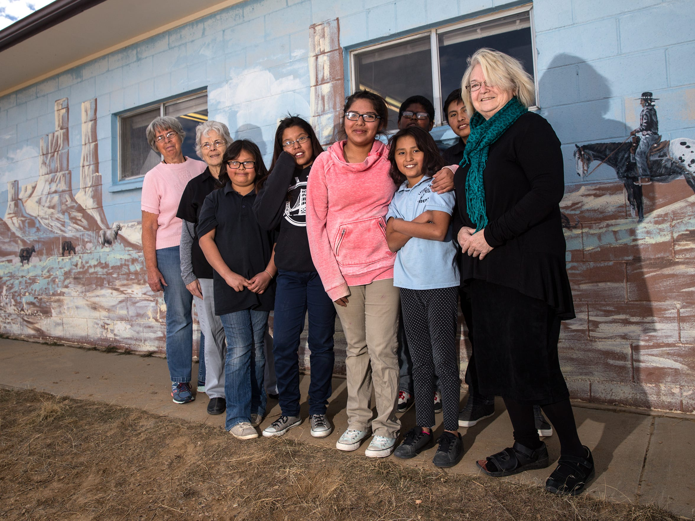 Claire Wilson James, right, poses with La Vida Mission school staff members and students Friday at the residential school south of Farmington.