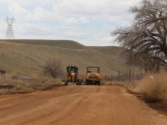 Crew members from the San Juan County Public Works Department continue work to improve the road surface of Navajo Route 362 on Tuesday in Lower Fruitland.