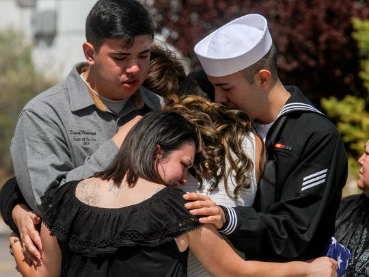 """Master Sgt. David Montoya's children, Nathanial """"Bear"""" Montoya, left, Kristin Montoya, Nicholas Montoya and his niece Cerena Hastings, bottom left, embrace Tuesday shortly after Master Sgt. David Montoya's memorial service at the New Mexico Army National Guard Armory in Farmington."""