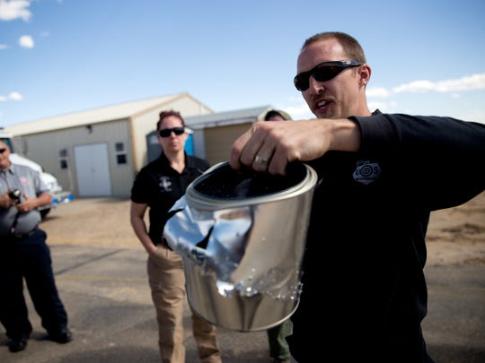 Bureau of Alcohol, Tobacco, Firearms and Explosives Special Agent Kevin Wolfe shows a can that contained black powder and was set off with a blasting cap during an explosive demonstration at Safety City in Kirtland.