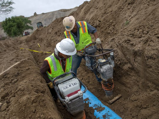 Laborer Baugn Saggboy, left, and Gadii'ahi Chapter President Harry Descheenie work on a pipeline project, Wednesday in Gadii'ahi.