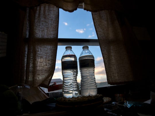 Samples of tap water collected in February sit on a table at Dusty March and Dawn Schumacher's home on Thursday in the Harvest Gold subdivision.