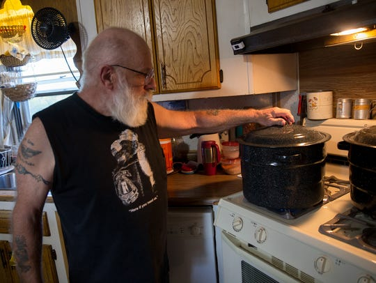 Dusty March boils a pot of water Thursday at his home