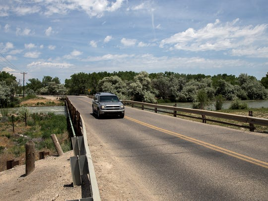 A vehicle crosses over the San Juan River Wednesday on County Road 5500 southwest of Bloomfield.