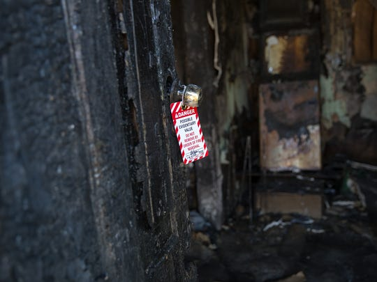 An evidence tag hangs on a door Tuesday at a burned-out house on East Broadway Avenue in Farmington.