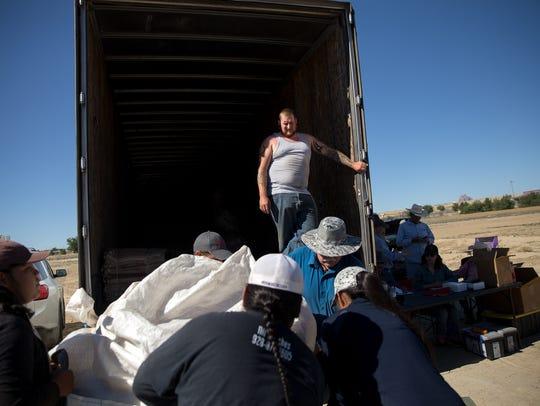Truck driver Sean Spellman, top, prepares to receive
