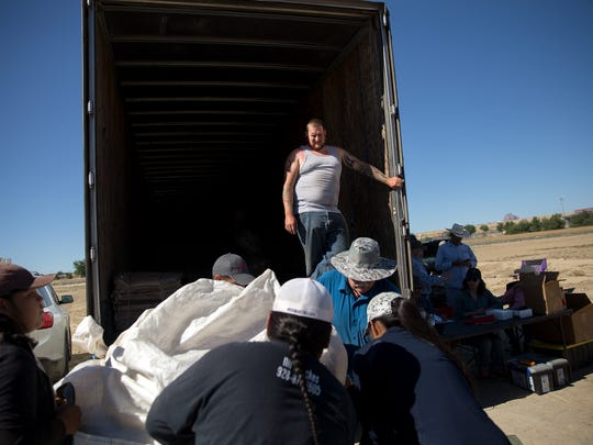 Truck driver Sean Spellman, top, prepares to receive a load of wool Tuesday during an annual wool and mohair buy event at Diné College in Shiprock.